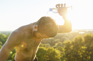 Barechested athlete pouring water over his head at sunset - DIGF001106