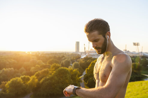 Barechested athlete with earbuds looking on watch at sunset - DIGF001115