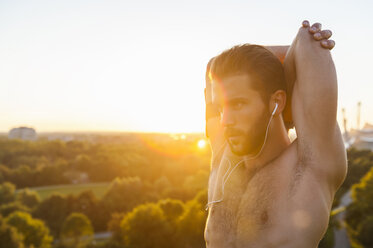 Barechested athlete stretching at sunset - DIGF001118