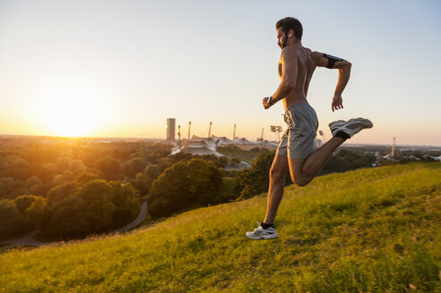 Barechested man running on meadow in park at sunset - DIGF001124