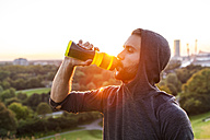 Athlete drinking from bottle at sunset - DIGF001130