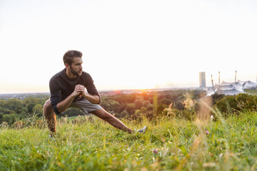 Athlete stretching on meadow at sunset - DIGF001133