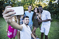 Friends taking a selfie in a garden during a summer party - ABZF001135
