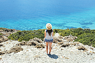 Greece, Cyclades islands, Amorgos, Woman with hat looking at the beautiful Aegean sea - GEMF000999