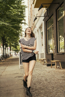 Germany, Berlin, laughing young woman walking on pavement - TAMF000611