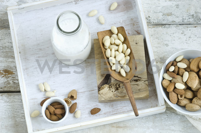 Glass bottle of homemade almond milk, whole and cracked almonds - ASF006011 - Achim Sass/Westend61