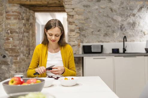 Woman in kitchen preparing fruit salad - DIGF001152