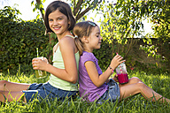 Two little sisters sitting back to back on a meadow drinking smoothies - LVF005258
