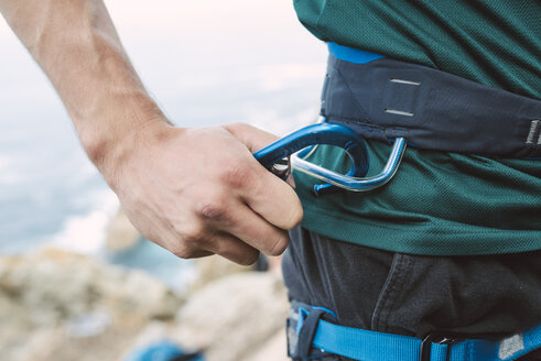 Close-up of climber placing a carabiner in his climbing harness - RAEF001453