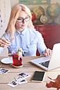 Woman working at home on laptop stirring tea with a sugar stick - RTBF000301