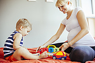 Pregnant mother and son playing on bed - ZEDF000317