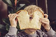 Little boy peeking through slice of white bread - MFF003018