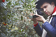 Man taking instant photography of berry bush - RTBF000317