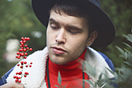 Young man looking at wild berries - RTBF000320