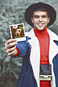 Man showing instant photography outdoors - RTBF000326