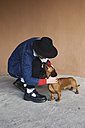 Young man petting his dachshund outdoors - RTBF000329