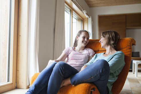 Happy mother and daughter sitting in armchair at home - RBF005162