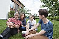 Happy family sitting in garden - RBF005195