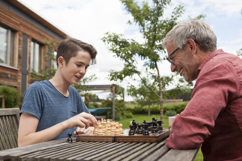 Father and son playing chess in garden - RBF005201