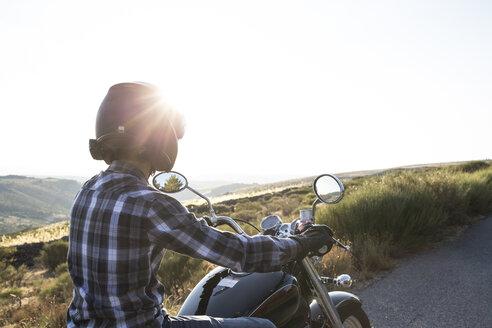 Man riding motorbike at evening twilight - ABZF001149