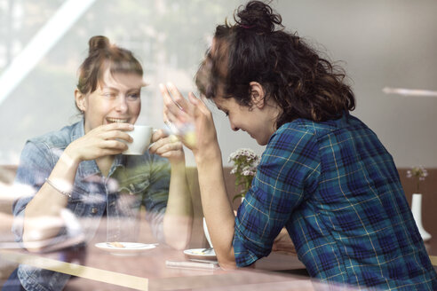 Two laughing women sitting behind windowpane of a coffee shop - TSFF000081