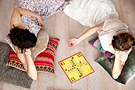 Top view of two best friends lying on the floor at home playing ludo - TSFF000111