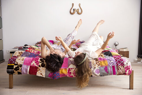 Two best friends lying on bed with legs in the air listening music with headphones - TSFF000114