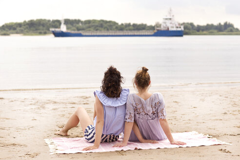 Back view of two friends sitting side by side on the beach watching a ship - TSFF000117