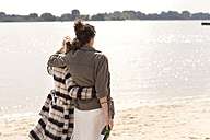 Back view of two friends walking arm in arm on the beach with bottle of sparkling wine - TSFF000126