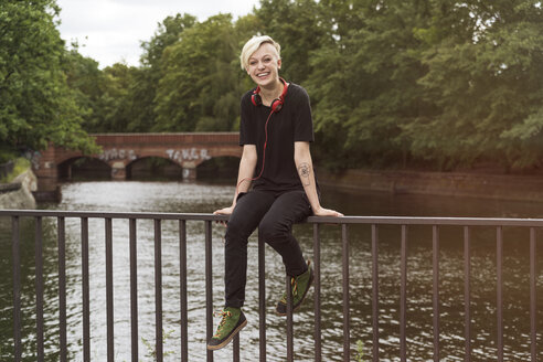 Laughing young woman sitting on railing in front of a canal - TAMF000620