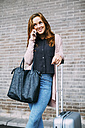 Smiling young woman with wheeled luggage and leather bag on the phone - EBSF001715