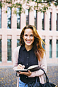 Portrait of smiling young woman with notebook - EBSF001718