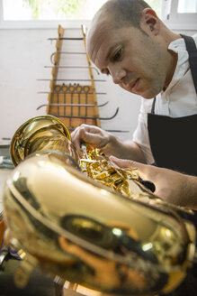 Instrument maker dismounting a saxophone during a repair - ABZF001162
