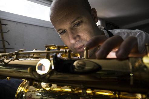 Instrument maker repairing a saxophone - ABZF001165