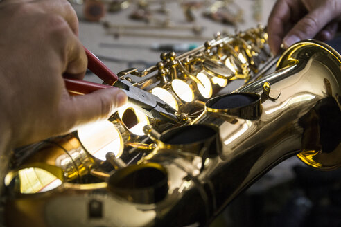 Instrument maker dismounting a saxophone using pliers during a repair - ABZF001168