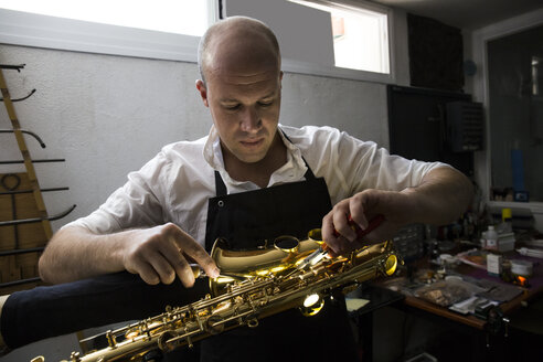 Instrument maker dismounting a saxophone during a repair - ABZF001171