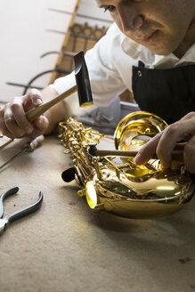 Instrument maker using a hammer repairing a saxophone - ABZF001174