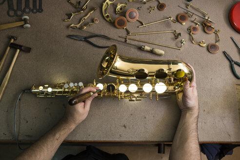 Instrument maker repairing a saxophone - ABZF001177