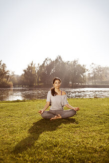 Woman with closed eyes relaxing in Lotus yoga pose - MFF003058