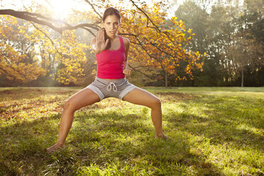 Woman holding a tai chi pose in autumnal park - MFF003061