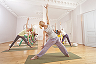 Group of people in yoga studio holding the extended triangle pose - MFF003067