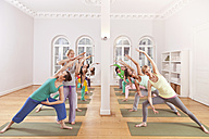 Group of people in yoga studio holding triangle pose - MFF003070