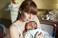 Mother holding her newborn baby in hospital room - MFF003127