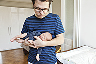 Father holding newborn son at home - MFF003130