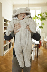 Baby in bear costume being held up by his father - MFF003148