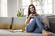 Smiling woman relaxing on couch holding a mug - MFF003172