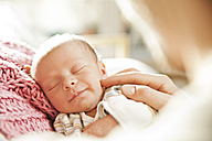 Sleeping newborn baby being touched by a hand - MFF003178