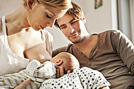 Mother breastfeeding her newborn baby with father watching - MFF003184