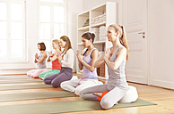 Group of women in yoga studio sitting in Lotus pose - MFF003205