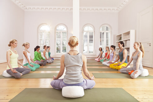 Group of people in yoga studio sitting in Lotus pose in front of instructor - MFF003208